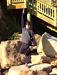 Modified tree pose on the rocks overlooking the Pacific Ocean in February.