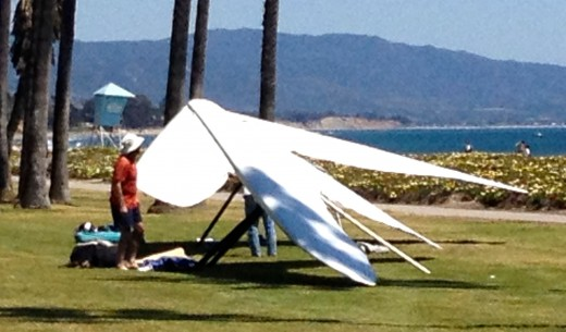 A guy inspecting his hang glider after a safe landing.