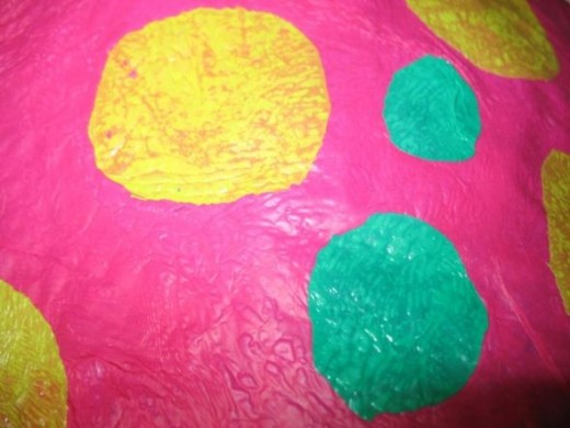 Yellow and green circles ironed on top of pink plastic bag.
