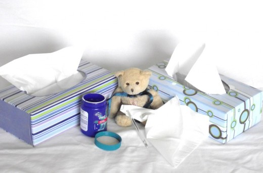Sick teddy bear surrounded by vaporub and tissue.