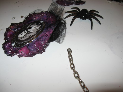 Broken jewelry completes the chain for the spider to hang from