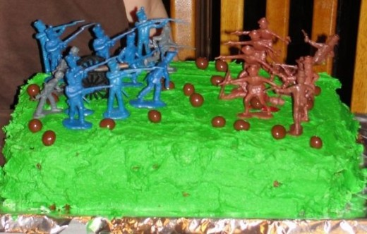 "This is probably the easiest option.  Add some green food coloring to vanilla frosting.  Top the cake with army men.  My oldest son decorated this.  He added peanut butter ball ""cannon balls"" and red icing ""blood."""