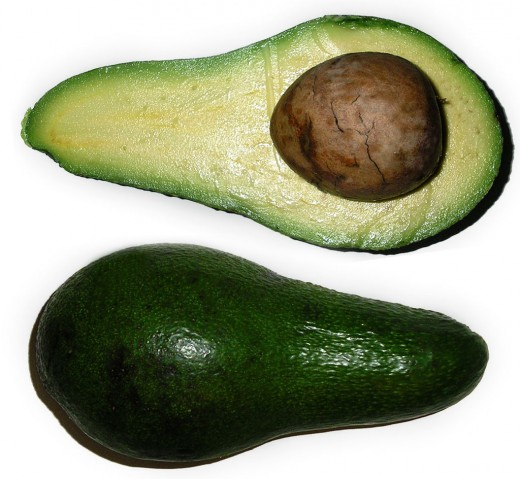 A sliced open avocado.  They are a fruit that is exceptionally high in nutritious fats.