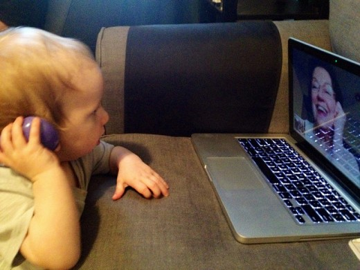 Child talking to grandmother using webcam