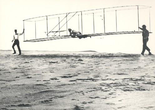 The Wright Brothers and an associate testing an early glider, the base for the Wright Flyer.