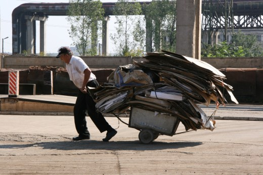 A man pulls a heavily loaded cart of salvaged construction discards