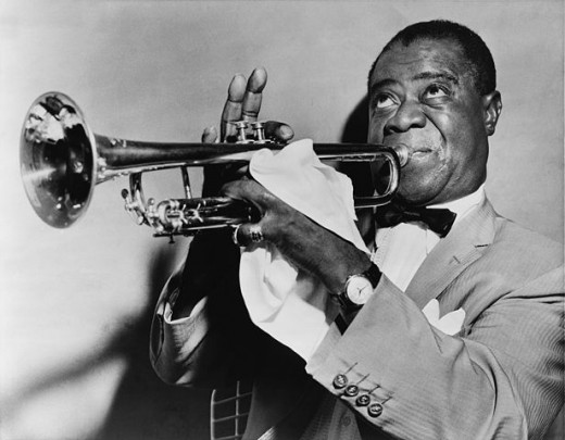 A picture of Louis Armstrong. Short-haired, black man in his fifties blowing into a trumpet. He is wearing a light-colored sport coat, a white shirt and a bow tie.