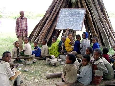 Due to insufficient learning tool, this teacher uses a small board to deliver his lesson.