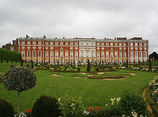 A view of the south facade of Hampton Court Palace with the formal garden in front of it.