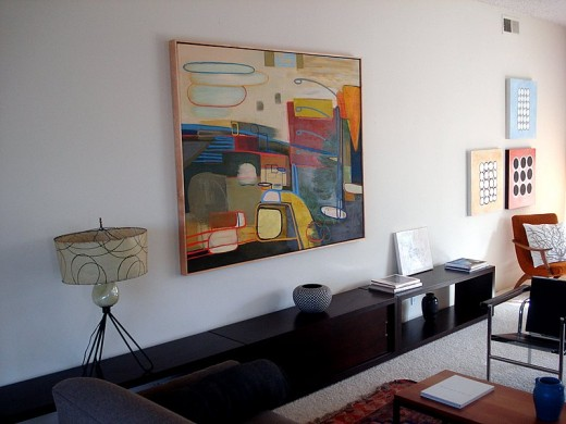 Displayed above is a large modern art painting in a modern living room.