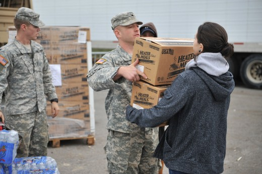 A soldier hands food rations to a Long Island survivor of Hurricane Sandy