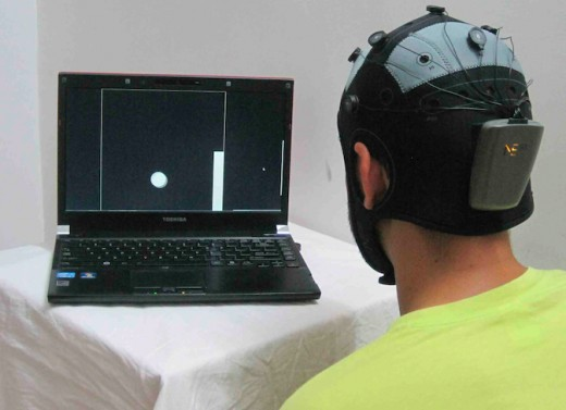 The test subject in India wearing a wireless EEG-headset & in the process of encoding EEG signals into binary information with the use of a computer display that reacts to brain signals. As each piece of the message is encoded it's emailed to France
