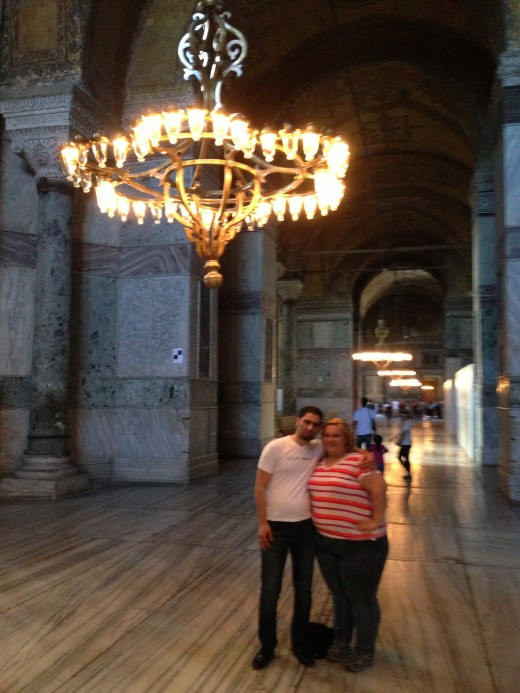 A couple poses under an ornate lighting located on the second floor of Aya Sophia.