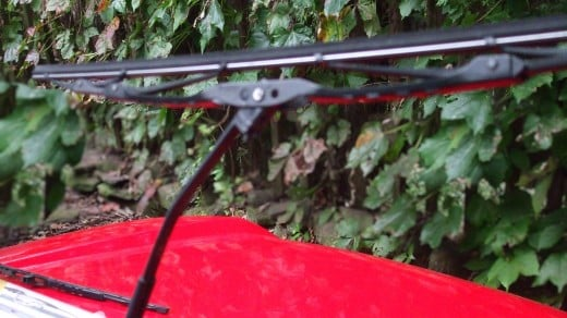 Windshield wiper arm is perpendicular to window and blade assembly is almost perpendicular to wiper arm.