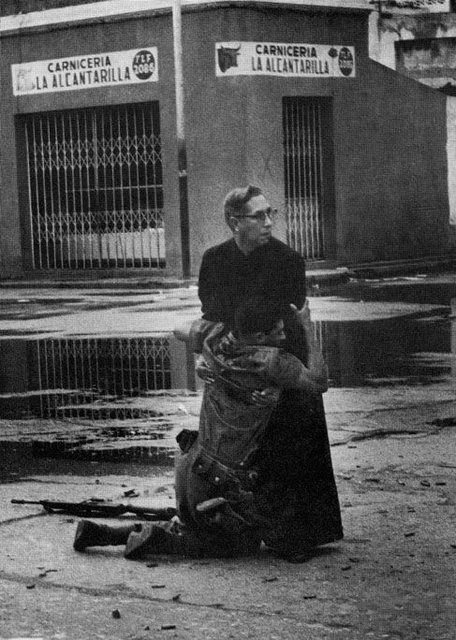 While under fire, Chaplain Louis Padillo was giving last rights to the dead in the streets in Venezuela, 1962 when this soldier grabbed him. http://www.pinterest.com/pin/84724036715325821/