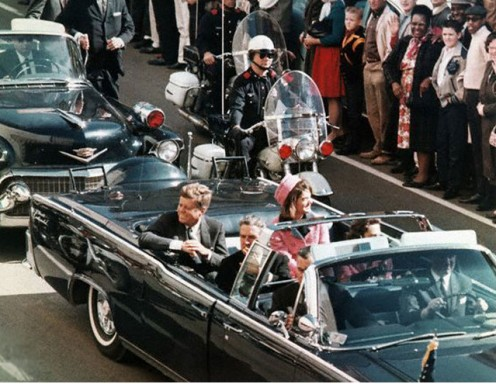 John F. Kennedy in a Ford Lincoln moments before the shots are fired. He is riding in Car 7. See the significance of this number in the photo below of the theatre box at the Ford Theatre.