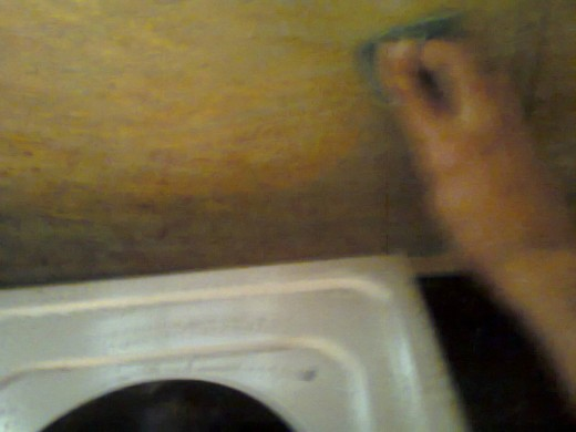 cleaning the walls around stove with scrubber