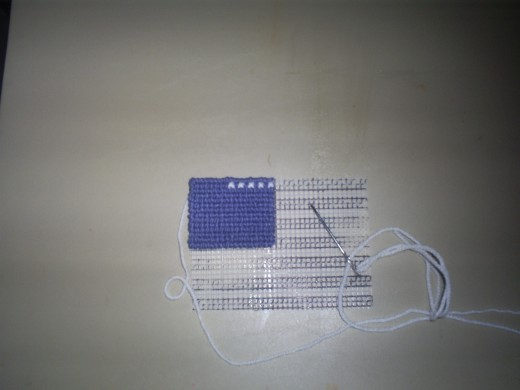 Begin cross stitching on all fifty white stars on the American flag.  As flags go I would say the United States, Kiribati, and Mexico have some of the most beautiful flags in the world, so cross stitching the American flag is truly art!