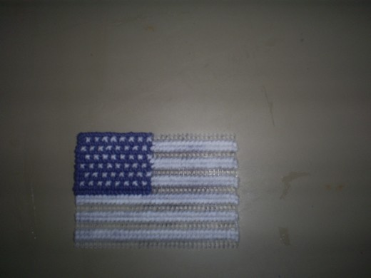 Here all the white stripes have been cross stitched on the American flag magnet.
