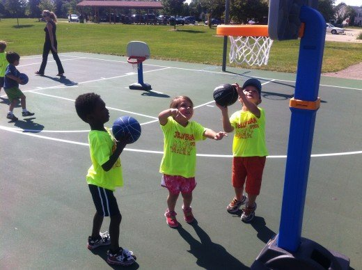 Young children shooting basketballs