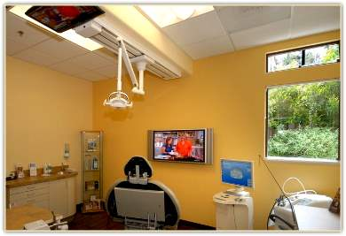 Dr. Fallah's treatment room has ceiling and wall-mounted TV along with state-of-the-art equipment and holistic methods for the best in dental care and comfort.
