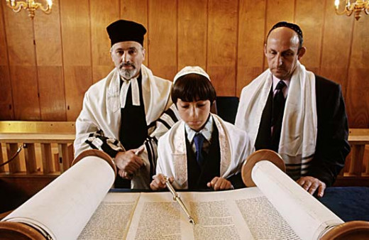 A Jewish boy reads from the Torah for the first time at his Bar Mitzvah.