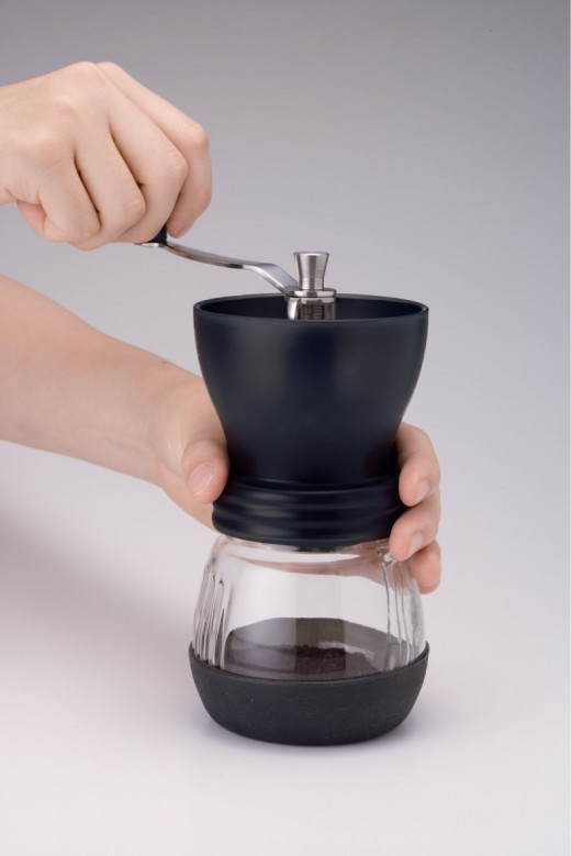 The Kyocera Ceramic is a top-rated inexpensive manual grinder that works well with coffee beans, as well as salt, pepper, green tea, and sesame seeds.  The Kyocera is easy to use and clean too, and needless to say, quiet.