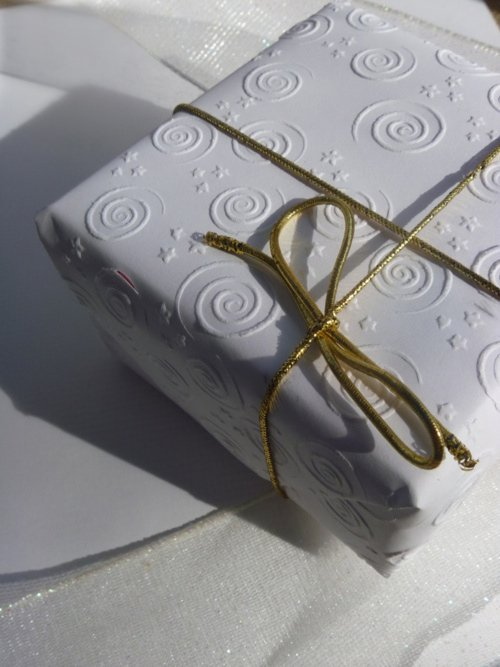 An elegant white present with a gold tie