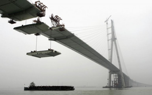 """The last pair of steel box girders is slung to be installed on the Sutong Bridge over the Yangtze River in east China's Jiangsu province May 29, 2007."""