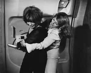 Brenda Vaccaro (R) puts a bear hug on Lee Grant (L) in Airport 1977