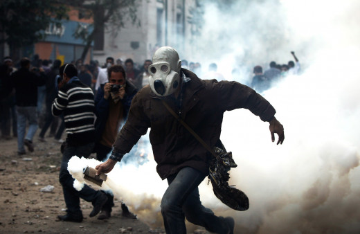 civilian running with tear gas cylinder after it was fired t them by the riot police