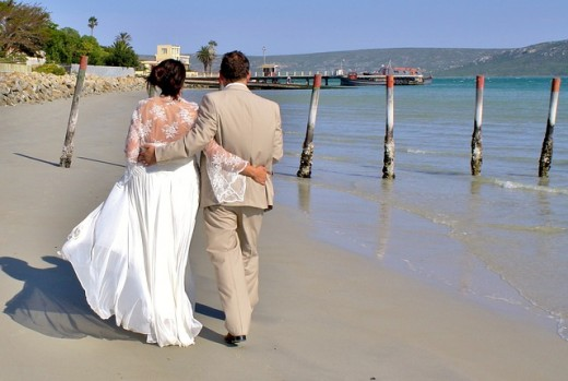 A bride and groom walk along the beach after a wedding ceremony.  50% of all marriages in the USA are estimated to end in divorce. Despite this, there are still plenty of people who choose to tie the knot, whether for romance, tradition, or religion.
