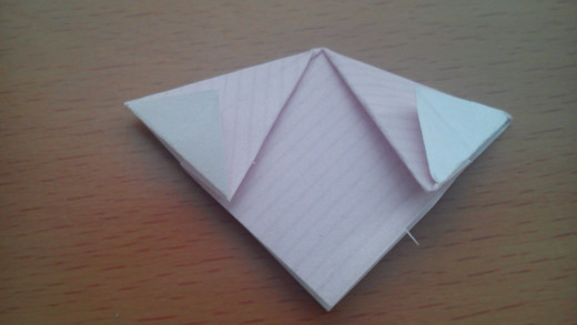Fold the tips back, so the crease is in line with the diamond shape below.