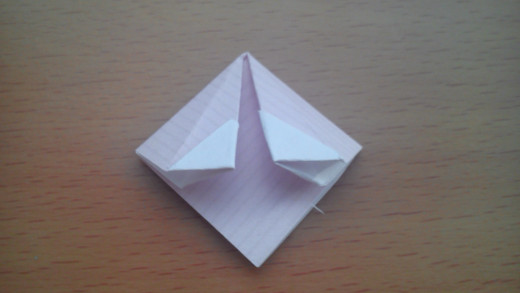 You should end up with a diamond like this. Dab some glue along one of these upper flaps, fold the diamond in half vertically so the flaps stick to each other.