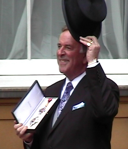 Sir Terry Wogan displaying his MBE.