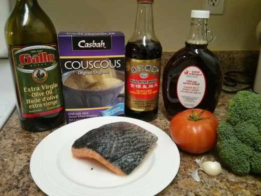 olive oil, couscous, soy sauce, maple syrup, salmon, tomato, garlic (and black pepper and dressing, not pictured)
