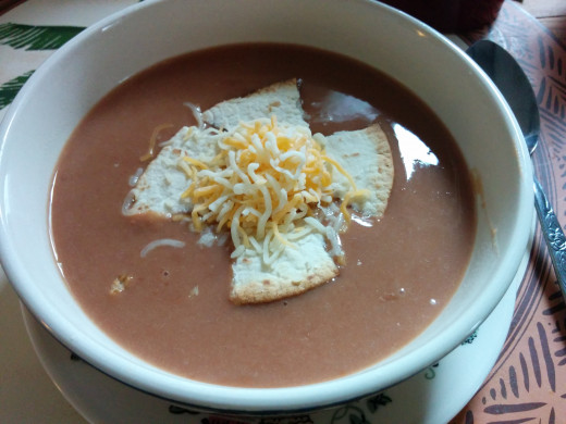 Creamy, rich refried bean soup with oven-crisped flour tortillas and a sprinkle of shredded cheese