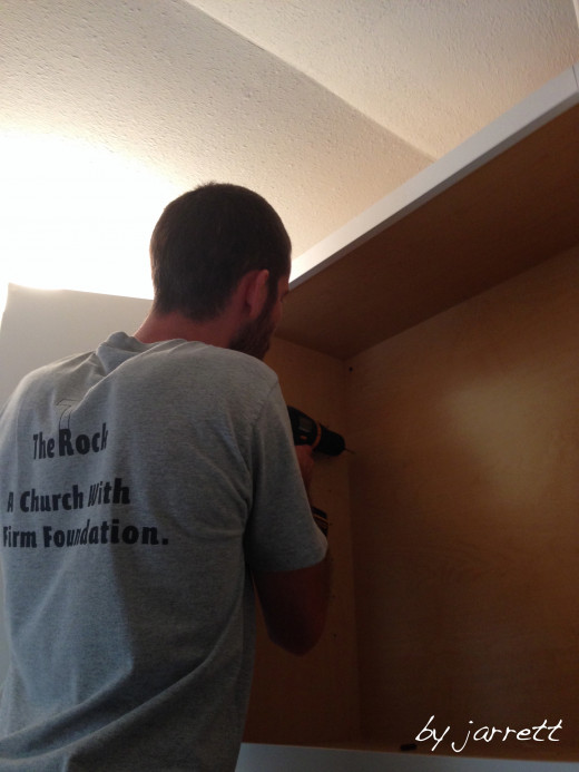 My husband finishing the cabinet installation