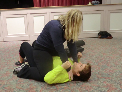 Two women from Savannah Strider's Track Club practice breaking free of a choke hold while on the ground and flipping their attacker over on their backs.