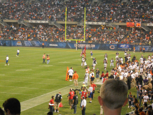 The players gathering around the officials by the sideline talking to them about a call on the field