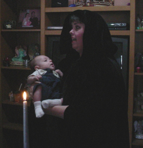 Priestess Sophia, a.k.a. Rev. Candy Lacey-Partlow officiating a Wiccaning (Baby Blessing Ceremony) for her grandson.