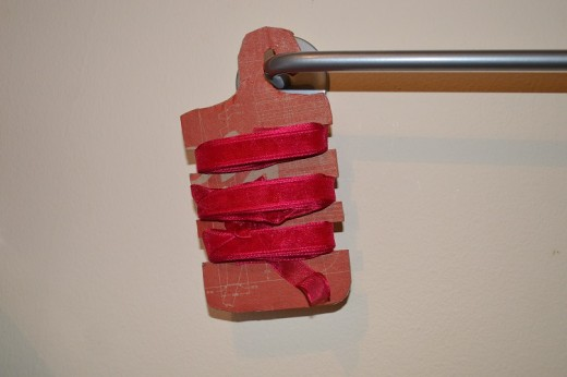 A shoe box that has been up-cycled into a hanging ribbon holder
