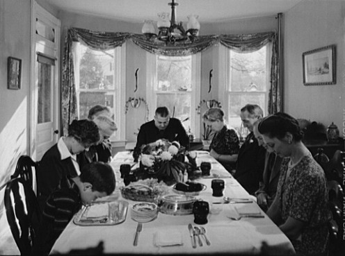 A classic picture of a family gathered around the table to pray and thank God for their blessings and food.