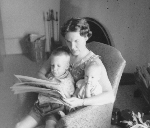 My mother, holding my brother & I while reading the newspaper