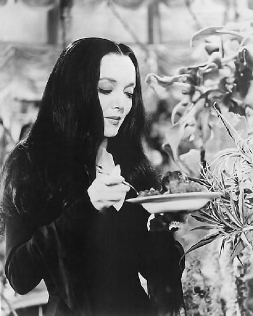 Morticia feeds Cleopatra, her man eating plant.