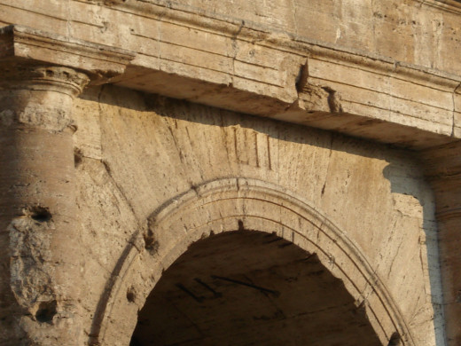 Roman numerals still showing above arch in the colosseum in Rome.