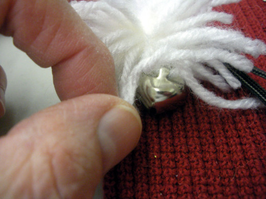 Tie the bell onto the yarn under the pom pom.  You did remember to leave extra length when you tied off the pom pom, right?