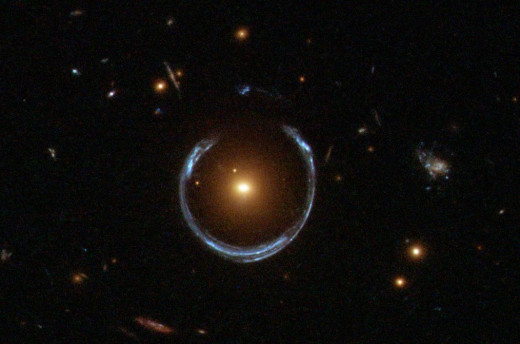 Gravitational Lensing in action. You can see the swirl of bluish light surrounding a bright point. The bright point is the site of a black hole (bright due to stars and other matter entering it and illuminating a concentrated area).