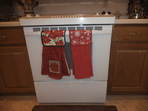 Having the towels and potholders buttoned over the oven door ensures they are close at hand and ready to use.