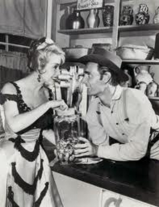 "Dennis Weaver, ""Chester Goode,"" enjoys a drink at the Long Branch Saloon on Gunsmoke"